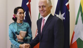 Myanmar's leader Aung San Suu Kyi, left, is welcomed to Parliament House by Australian Prime Minister Malcolm Turnbull during her state visit in Canberra Monday, March 19,2018. The Nobel Peace laureate who has been widely condemned over her country's treatment of its Rohingya Muslim minority arrived in Sydney at the weekend for a summit of Southeast Asian leaders. (Mick Tsikas/AAP Image via AP)