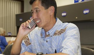 FILE - This Nov. 4, 2014 file photo former US Congressman Charles Djou, Republican candidate for the Hawaii US House seat, makes some last minute campaign phone calls at his headquarters on election day in Honolulu. Djou, says he's leaving the Republican Party because of President Donald Trump and the failure of fellow party members to stand up to him. Djou represented Honolulu in the U.S. House from 2010 to 2011. He wrote in an opinion piece published in Civil Beat on Monday, March 19, 2018, that he's disturbed that the Republican Party under Trump has become hostile to immigration. (AP Photo/Marco Garcia, File)