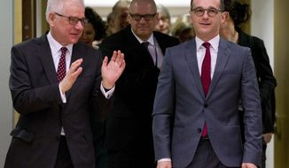 CAPTION CORRECTS POLISH FOREIGN MINISTER'S FIRST NAME FROM JACK TO JACEK Polish Foreign Minister Jacek Czaputowicz, left, speaks with German Foreign Minister Heiko Maas during a round table meeting of EU foreign ministers at the Europa building in Brussels on Monday, March 19, 2018. European Union foreign ministers on Monday are set to discuss Ukraine, Syria, Korea and Iran. (AP Photo/Virginia Mayo)
