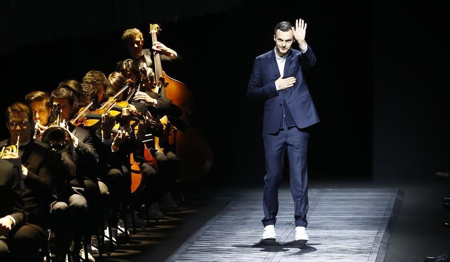 FILE - In this Saturday, Jan. 24, 2015 file photo, Belgian fashion designer Kris van Assche waves after the presentation of Dior's men's fall-winter 2015/2016 collection presented in Paris, France. Christian Dior has announced on Monday, March 19, 2018 that its long-time menswear designer Kris Van Assche is to leave the Parisian fashion house. (AP Photo/Jacques Brinon, File)