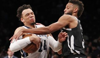 Brooklyn Nets guard Allen Crabbe (33) tries to strip the ball from Memphis Grizzlies forward Dillon Brooks (24) as Brooks drives to the basket during the first half of an NBA basketball game, Monday, March 19, 2018, in New York. (AP Photo/Kathy Willens)