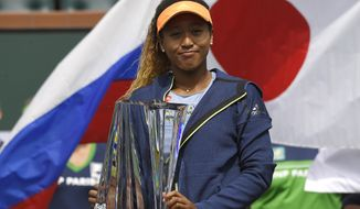 Naomi Osaka, of Japan, poses with her trophy after defeating Daria Kasatkina, of Russia, in the women's final at the BNP Paribas Open tennis tournament, Sunday, March 18, 2018, in Indian Wells, Calif. Osaka won 6-3, 6-2. (AP Photo/Mark J. Terrill)