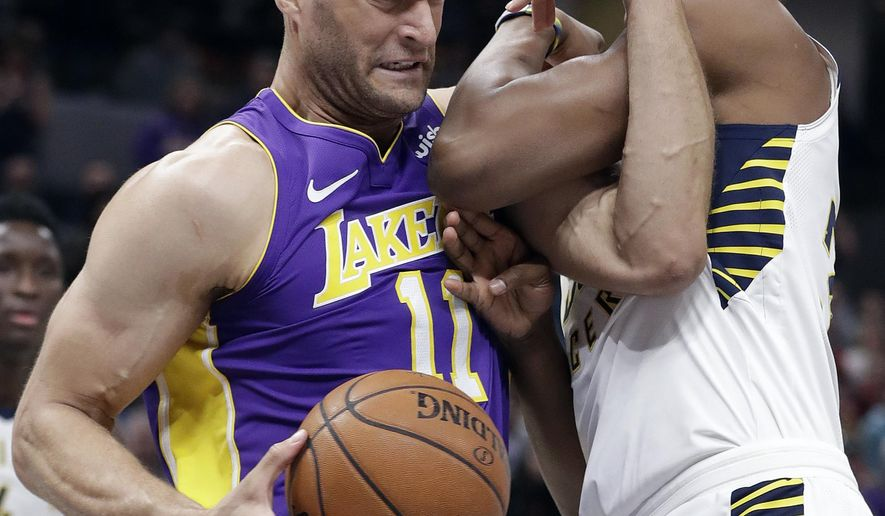 Los Angeles Lakers' Brook Lopez, left, goes to the basket against Indiana Pacers' Myles Turner during the first half of an NBA basketball game, Monday, March 19, 2018, in Indianapolis. (AP Photo/Darron Cummings)