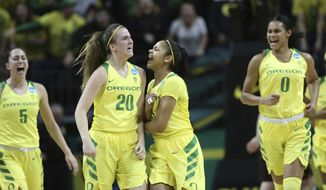 Oregon's Maite Cazorla, Sabrina Ionescu, Justine Hall and Satou Sabally, from left, celebrate a buzzer-beating 3-point shot by Ionescu during the first half of a second-round game against Minnesota in the NCAA women's college basketball tournament in Eugene, Ore., Sunday, March 18, 2018. (AP Photo/Chris Pietsch)