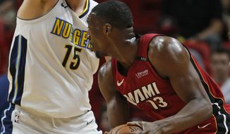 Miami Heat center Bam Adebayo (13) looks for an opening past Denver Nuggets center Nikola Jokic (15) during the first half of an NBA basketball game, Monday, March 19, 2018, in Miami. (AP Photo/Wilfredo Lee)