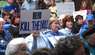 In this Feb. 14, 2018 photo, people hold signs protesting President Donald Trump's plan to allow offshore oil and gas drilling along most of the nation's coastline at a hearing Hamilton, N.J. Some coastal states including New Jersey that oppose President Donald Trump's plan to allow offshore drilling in deeper federal waters along most of the nation's coastline are using state-level laws to try to make it difficult or impossible to conduct drilling in their areas by banning pipelines or other drilling infrastructure in state waters. (AP Photo/Wayne Parry)