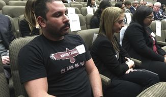 Shane Fedderman, left, a 1998 graduate of Marjory Stoneman Douglas High School in Parkland, Fla., watches as families of mass shooting victims urge California's public pension funds to stop investing in retailers of assault weapons in Sacramento, Calif., on March 19, 2018. Fedderman, who lives in Hollywood, is one of several alumni of the high school, where 17 people were killed in February, calling on the fund to divest from gun retailers. (AP Photo/Kathleen Ronayne)