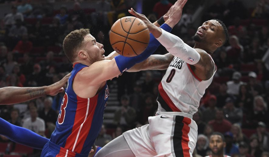Portland Trail Blazers guard Damian Lillard is defended by Detroit Pistons forward Blake Griffin, left, during the second half of an NBA basketball game in Portland, Ore., Saturday, March 17, 2018. The Blazers won 100-87. (AP Photo/Steve Dykes)