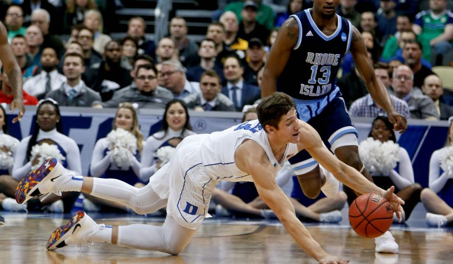 Duke's Grayson Allen bottom, dives for a loose ball in front of Rhode Island's Stanford Robinson (13) during the first half of a second-round game in the NCAA men's college basketball tournament, Saturday, March 17, 2018, in Pittsburgh. (AP Photo/Keith Srakocic)