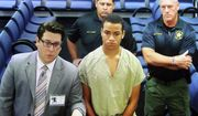 Zachary Cruz, center, the brother of the Florida school shooting suspect, is displayed in a monitor via closed circuit television from the main jail as he as he makes his first appearance on charges of trespassing on the grounds of Marjory Stoneman Douglas High School, Tuesday, March 20, 2018, at the Broward County Courthouse in Fort Lauderdale, Fla. A judge set an unusually high $500,000 bond on Tuesday and imposed a host of other restrictions. (Amy Beth Bennett/South Florida Sun-Sentinel via AP, Pool)
