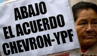 """A woman holds a banner that reads in Spanish; """"Down with the Chevron- YPF agreement,"""" during a protest in Buenos Aires, Argentina, Wednesday, May 21, 2014. Demonstrators gathered to protest against a joint venture between YPF and Chevron to use hydraulic fracturing or """"fracking"""" at a major shale oil and gas deposit known as """"Vaca Muerta."""" (AP Photo/Natacha Pisarenko)"""