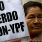 "A woman holds a banner that reads in Spanish; ""Down with the Chevron- YPF agreement,"" during a protest in Buenos Aires, Argentina, Wednesday, May 21, 2014. Demonstrators gathered to protest against a joint venture between YPF and Chevron to use hydraulic fracturing or ""fracking"" at a major shale oil and gas deposit known as ""Vaca Muerta."" (AP Photo/Natacha Pisarenko)"