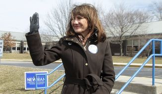 Marie Newman, 3rd district Democratic candidate, waves to a supporter as she stands in front of Kolmar Elementary School in Oak Lawn, Ill., on Tuesday, March 20, 2018.   Newman is challenging seven-term Democratic Rep. Dan Lipinski.  (Leslie Adkins/Chicago Sun-Times via AP)