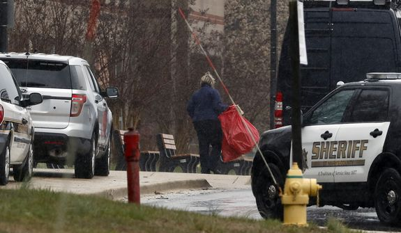 A bag is removed and taken to the crime scene van at Great Mills High School, the scene of a shooting, Tuesday, March 20, 2018, in Great Mills. A student with a handgun shot two classmates inside the school before he was fatally wounded during a confrontation with a school resource officer, a sheriff said.  (AP Photo/Alex Brandon)