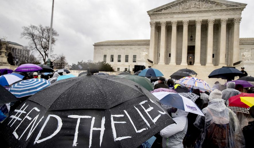 """A pro-abortion rights supporter holds an umbrella that reads """"#EndTheLies"""" during a rally outside the Supreme Court in Washington, Tuesday, March 20, 2018, as the Supreme Court hears arguments in a free speech fight over California's attempt to regulate anti-abortion crisis pregnancy centers. (AP Photo/Andrew Harnik)"""