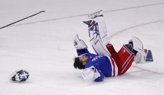 New York Rangers goaltender Henrik Lundqvist loses his mask as he hits the ice after being upended on a play during the third period of the team's NHL hockey game against the Columbus Blue Jackets, Tuesday, March 20, 2018, in New York. The Blue Jackets won 5-3. (AP Photo/Julie Jacobson)
