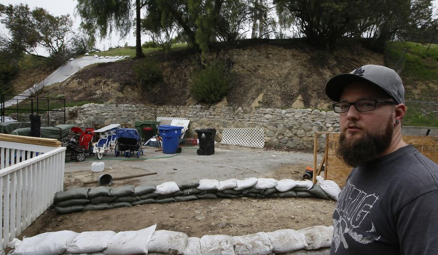 Andrew Joos-Visconti protects his home from the upcoming rains with sand bags in the Sun Valley area of Los Angeles Tuesday, March 20, 2018. Authorities ordered tens of thousands of people to flee their homes as a powerful storm headed toward California, where many communities on Tuesday face the threat of flooding and destructive debris flows from areas burned bare by huge wildfires. (AP Photo/Damian Dovarganes)