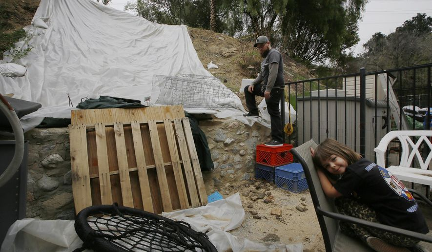 Andrew Joos-Visconti works to protect his back yard from the upcoming rains with a plastic tarp, in the Sun Valley area of Los Angeles Tuesday, March 20, 2018. At right, his daughter, Scarlett, 4. Authorities ordered tens of thousands of people to flee their homes as a powerful storm headed toward California, where many communities on Tuesday face the threat of flooding and destructive debris flows from areas burned bare by huge wildfires. (AP Photo/Damian Dovarganes)