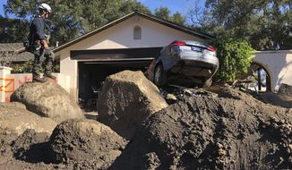 FILE - In this Jan. 13, 2018, file photo provided by the Santa Barbara County Fire Department, Capt. John Pepper, Fresno Fire Department, and Rescue Squad Leader RTF-5 searches homes off East Valley Road in Montecito, Calif. Authorities are urging people living in an area devastated by mudslides to evacuate ahead of a strong Pacific storm that forecasters say is likely to bring an extended period of rain and the threat of flooding and debris flows. Santa Barbara County issued a mandatory evacuation order Monday, March 19, 2018, affecting about 30,000 people, including the community of Montecito, where 21 people were killed by a massive mudslide in January. (Mike Eliason/Santa Barbara County Fire Department via AP, File)