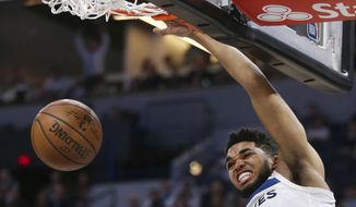 Minnesota Timberwolves forward Karl-Anthony Towns dunks in front of Los Angeles Clippers guard Milos Teodosic (4) in the second quarter of an NBA basketball game Tuesday, March 20, 2018, in Minneapolis. (AP Photo/Andy Clayton-King)