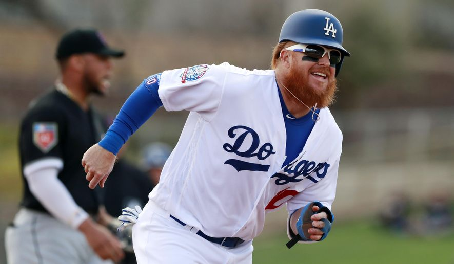 FILE - In this Friday, Feb. 23, 2018, file photo, Los Angeles Dodgers' Justin Turner runs to third from second after a throwing error by Chicago White Sox second baseman Yoan Moncada during the third inning of a baseball spring exhibition game, in Glendale, Ariz. Turner has a broken left wrist after being hit by a pitch during a spring training game, Monday, March 19, 2018. (AP Photo/Carlos Osorio, File)