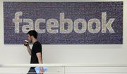 FILE - In this March 15, 2013, file photo, a Facebook employee walks past a sign at Facebook headquarters in Menlo Park, Calif. The San Jose Mercury News reports Saturday, March 17, 2018 that building permits compiled by Buildzoom show Facebook plans to erect the 465,000 square-foot (43,200 square-meter) building at its campus in Menlo Park, Calif. (AP Photo/Jeff Chiu, File)