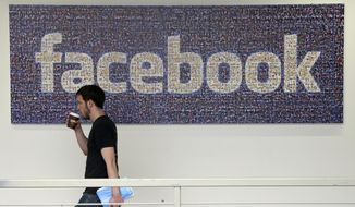 In this March 15, 2013, file photo, a Facebook employee walks past a sign at Facebook headquarters in Menlo Park, Calif. (AP Photo/Jeff Chiu, File)
