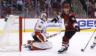Arizona Coyotes left wing Max Domi (16) celebrates his goal against the Calgary Flames goaltender Mike Smith (41) during the second period of an NHL hockey game Monday, March 19, 2018, in Glendale, Ariz. (AP Photo/Ross D. Franklin)