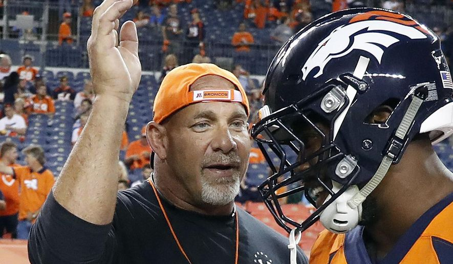 In this Sept. 11, 2017, file photo, professional wrestler Bill Goldberg, left, greets Denver Broncos outside linebacker Von Miller prior to an NFL football game against the Los Angeles Chargers, Monday, Sept. 11, 2017, in Denver. (AP Photo/Jack Dempsey, File)