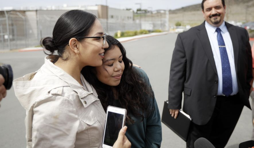 Chantal Estrada, center, a daughter of Perla Morales Luna, hugs family friend Judith Castro, left, as attorney Andres Moreno looks on, right, in front of the Otay Mesa Detention Center Tuesday, March 20, 2018, in San Diego. Morales Luna, a Mexican woman whose videotaped arrest for being in the U.S. illegally gained widespread attention online, is being released on her own recognizance by an immigration judge in Southern California. (AP Photo/Gregory Bull)