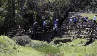 Jordan Spieth, center, and Dustin Johnson, center right, cross a pedestrian bridge on the fourth hole during a practice round at the Dell Technologies Match Play golf tournament at the Austin Country Club, Tuesday, March 20, 2018, in Austin, Texas. (AP Photo/Eric Gay)