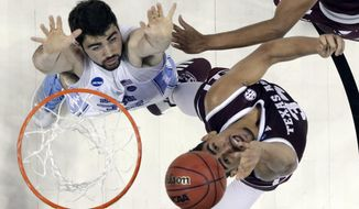 Texas A&M's Tyler Davis, right, shoots past North Carolina's Luke Maye, left, during the second half of a second-round game in the NCAA men's college basketball tournament in Charlotte, N.C., Sunday, March 18, 2018. (AP Photo/Bob Leverone)