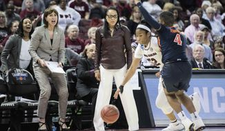 South Carolina head coach Dawn Staley, center, watches Tyasha Harris (52) dribble the ball against Virginia guard Dominique Toussaint (4) during the first half of a second-round game of the NCAA women's college basketball tournament, Sunday, March 18, 2018, in Columbia, S.C. South Carolina defeated Virginia 66-56. (AP Photo/Sean Rayford)