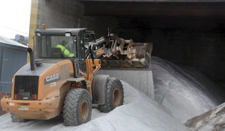 A heavy equipment operator with the Hazleton Department of Public Works uses a loader to move anti-skid material as the city along with other municipalities and the state gear up for another winter storm on Tuesday, March 20 ,2018 in Hazleton, Pa.   (Ellen F. O'Connell/Hazelton Standard-Speaker via AP)