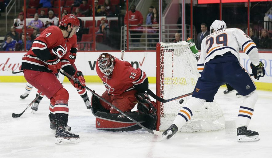Carolina Hurricanes' Haydn Fleury (4) and goalie Scott Darling (33) defend the goal against Edmonton Oilers' Leon Draisaitl, of Germany, during the first period of an NHL hockey game in Raleigh, N.C., Tuesday, March 20, 2018. (AP Photo/Gerry Broome)