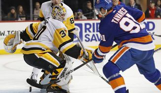 New York Islanders center John Tavares (91) threatens to score behind Pittsburgh Penguins goaltender Matt Murray (30) as Penguins defenseman Brian Dumoulin (8) watches during the second period of an NHL hockey game in New York, Tuesday, March 20, 2018. (AP Photo/Kathy Willens)