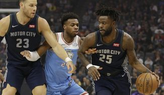 Sacramento Kings guard Buddy Hield, center, tries to fight through the screen set by Detroit Pistons forward Blake Griffin, left, as he guards Pistons forward Reggie Bullock, right during the first half of an NBA basketball game Monday, March 19, 2018, in Sacramento, Calif. (AP Photo/Rich Pedroncelli)
