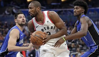 Toronto Raptors' Serge Ibaka, center, looks for a way to the basket as he gets between Orlando Magic's Nikola Vucevic, left, and Jonathan Isaac, right, during the first half of an NBA basketball game, Tuesday, March 20, 2018, in Orlando, Fla. (AP Photo/John Raoux)