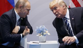 FILE - In this file photo taken on Friday, July 7, 2017, U.S. President Donald Trump, right, meets with Russian President Vladimir Putin at the G-20 Summit in Hamburg, Germany. On March 21, Mr. Trump lashed out at critics in the 'crazed' media for congratulating Mr. Putin on the occasion of his reelection to the presidency, a process democracy watchdogs say was not a fair contest. (AP Photo/Evan Vucci)
