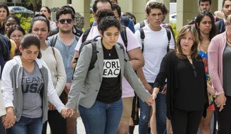 Florida International University students observe a moment of silence for the victims of the bridge collapse at the school four days earlier, Monday, March 19, 2018, in Miami. (Daniel A. Varela/Miami Herald via AP)