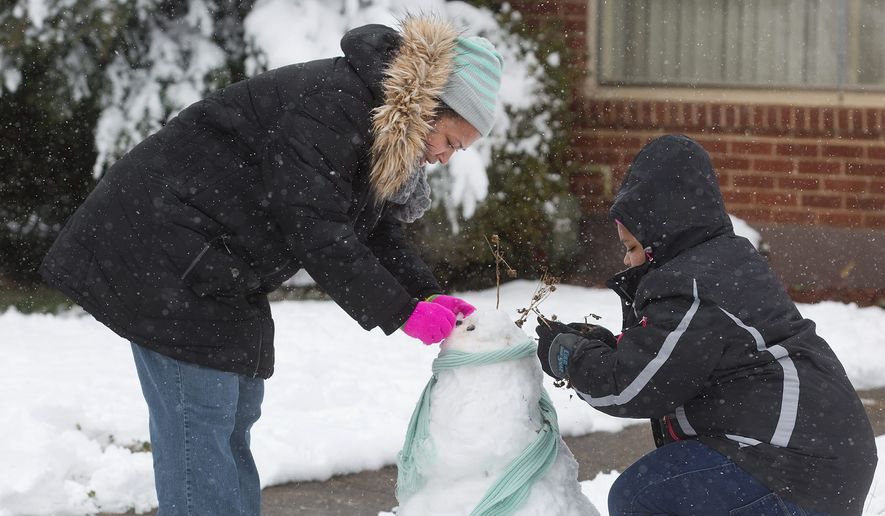 Sherry and Heavyn Eanes make a snowman in their front yard in Northwest Roanoke, Virginia, Wednesday. Schools and governments were shut down after a nor'easter dropped up to seven inches of snow in the D.C. area. (ASSOCIATED PRESS)