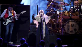 FILE - In this Jan. 26, 2018, file photo, singer Stevie Nicks, center, John McVie and Mick Fleetwood, right, of Fleetwood Mac perform at the 2018 MusiCares Person of the Year tribute honoring Fleetwood Mac in New York. On Wednesday, March 21, the Librarian of Congress announced Fleetwood Mac as inductees into the National Recording Registry. (Photo by Evan Agostini/Invision/AP, File)