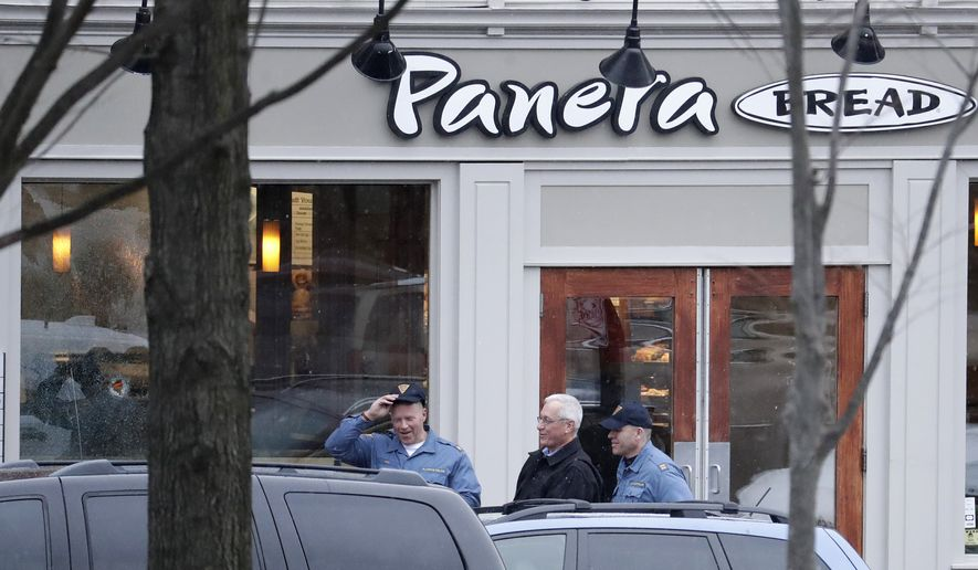 A hole is seen on the glass panel, far left, as New Jersey State Police officials walk out of a Panera Bread restaurant in Princeton, N.J., where an armed man was holed up across the street from Princeton University's campus, Tuesday, March 20, 2018. (AP Photo/Julio Cortez)