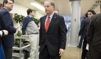 """Sen. Doug Jones, D-Ala., heads to the Senate to vote on the bipartisan """"Stop Enabling Sex Traffickers Act"""" which would allow victims of sex trafficking to sue websites that enabled their abuse, on Capitol Hill in Washington, Wednesday, March 21, 2018. In his maiden speech to the Senate today, Jones said the nation has reached a """"tipping point"""" on gun violence following the mass shooting at a Florida high school and Congress must address gun violence, even as lawmakers protect the Second Amendment rights of gun owners. (AP Photo/J. Scott Applewhite)"""