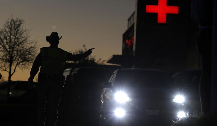 Texas troopers help redirect traffic near the site of another explosion, Tuesday, March 20, 2018, in Austin, Texas. Emergency teams were responding  to another reported explosion in Texas' capital, this one at a Goodwill store in the southern part of the city. (Jan Janner/Austin American-Statesman via AP)