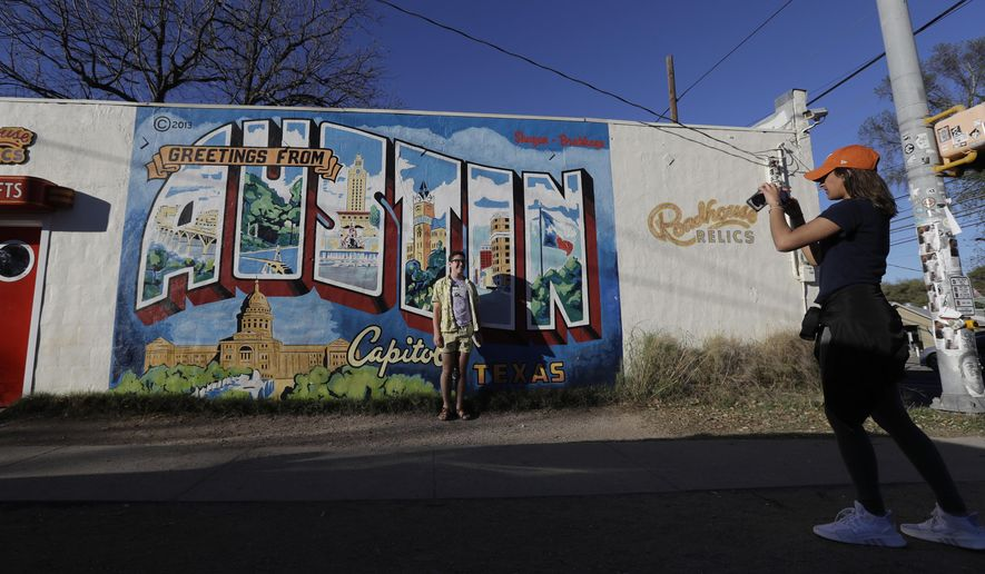 Visitors take photos at a popular mural, Tuesday, March 20, 2018, in Austin, Texas, a city that has seen five bombings that have killed two people and badly wounded four others since March 2. The recent blasts have sent a deep chill through a hipster city known for warm weather, live music, barbeque and, above all, not taking itself too seriously. (AP Photo/Eric Gay)