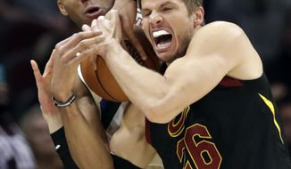 Milwaukee Bucks' Giannis Antetokounmpo, back, from Greece, fouls Cleveland Cavaliers' Kyle Korver in the second half of an NBA basketball game, Monday, March 19, 2018, in Cleveland. The Cavaliers won 124-117. (AP Photo/Tony Dejak)