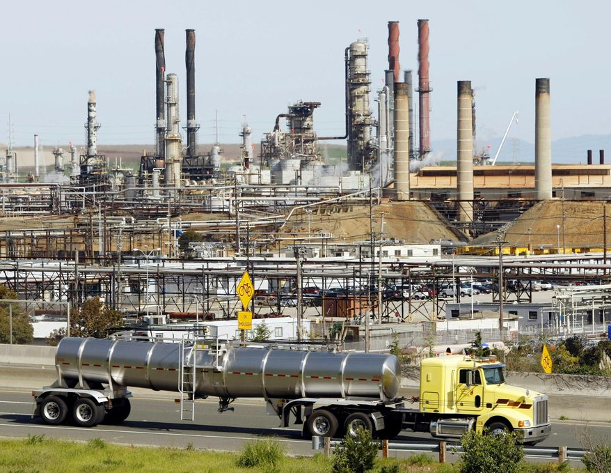 """This March 9, 2010 file photo shows a tanker truck passing the Chevron oil refinery in Richmond, Calif. A federal judge presiding over lawsuits accusing big oil companies of lying about global warming is turning his courtroom into a classroom. U.S. District Judge William Alsup has asked lawyers for two California cities and five of the world's largest oil and gas companies to come to court on Wednesday, March 21, 2018, to present """"the best science now available on global warming."""" (AP Photo/Paul Sakuma, File)"""