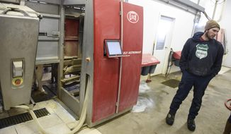 In a Tuesday, March 6, 2018 photo, Isaak Hinnenkamp talks about the operation of robotic milking equipment during a tour of his farm near Melrose, Minn. (Dave Schwarz/St. Cloud Times via AP)