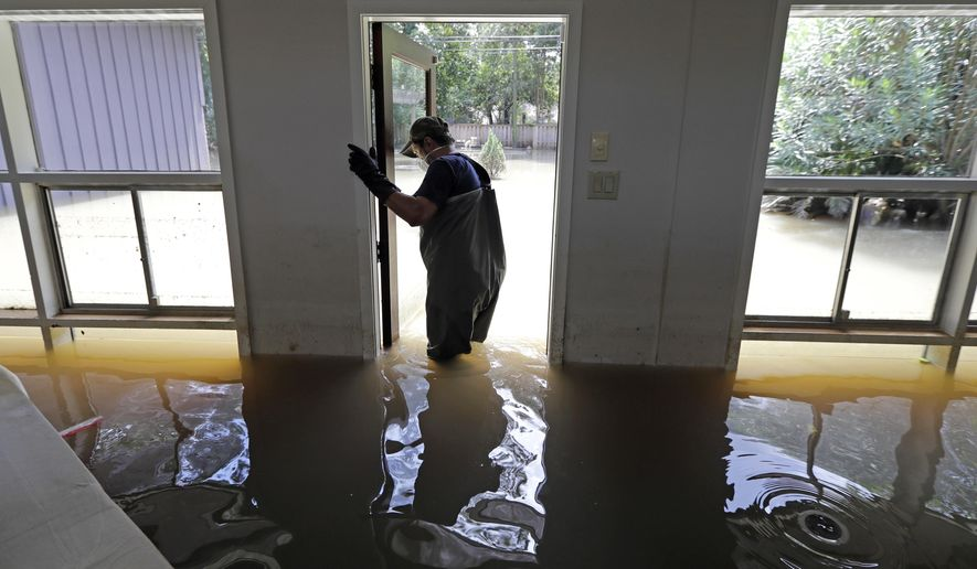 FILE - In this Sept. 4, 2017, file photo, Juan Minutella opens the back door while helping friend Gaston Kirby collect the last of his belongings from his flooded home in the aftermath of Hurricane Harvey in Houston. A new report indicates more than 80 percent of the homes in Houston's floodplains that were damaged by Hurricane Harvey would have been spared if they were at the higher elevation Mayor Sylvester Turner has proposed for future development in those flood-prone areas. (AP Photo/David J. Phillip, File)